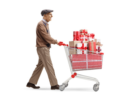 Full length profile shot of a senior man pushing a shopping cart full of wrapped presents isolated on white background