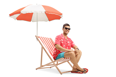 Full length shot of a young man sitting on a deckchair under an umbrella and smiling at the camera isolated on white background