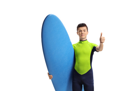 Young male surfer with a surfboard making a thumb up gesture isolated on white background Reklamní fotografie