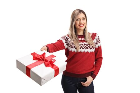 Young cheerful woman wearing a red sweater and holding a present isolated on white background