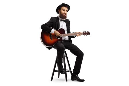 Full length shot of a male musician sitting and playing an acoustic guitar isolated on white background