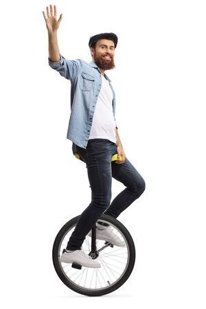 Full length shot of a bearded guy on a unicycle waving at the camera isolated on white background