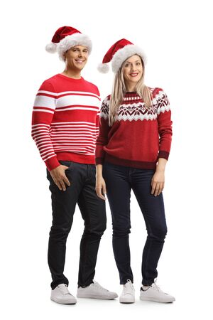 Full length portrait of a young man and woman wearing a christmas santa hat and sweaters isolated on white background