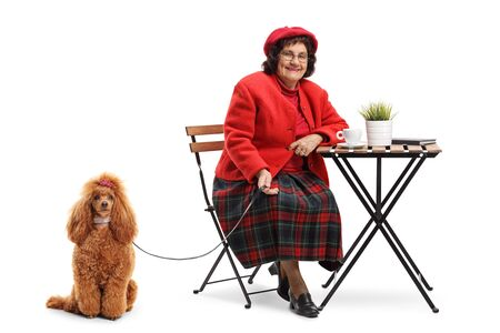 Full length portrait of a senior lady sitting in a cafe with a groomed red poodle isolated on white background