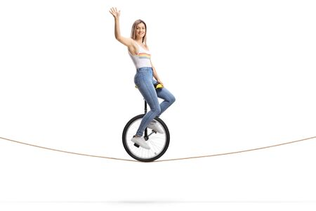 Full length shot of a woman riding a unicycle on a rope and waving at the camera isolated on white background Reklamní fotografie