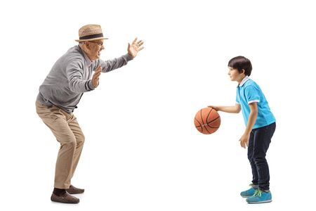 Full length shot of grandfather playing basketball with his grandson isolated on white background