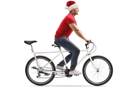 Full length profile shot of a young man wearing a santa claus hat and riding a tandem bicycle isolated on white background