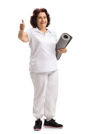 Full length portrait of a senior woman with an exercise mat showing thumbs up isolated on white background