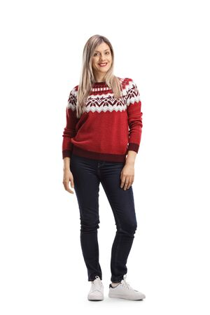 Full length portrait of a young blond female wearing a christmas red sweater and posing isolated on white background