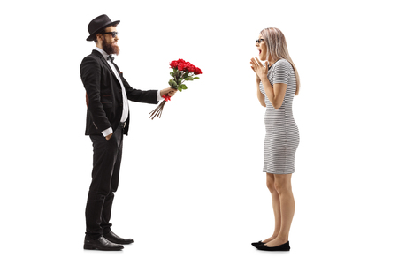 Full length profile shot of a man in a suit giving a bouquet of red roses to a surprised woman isolated on white background