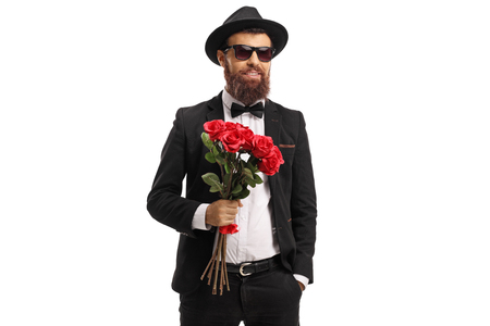 Bearded man in a suit holding a bouquet of red roses isolated on white background