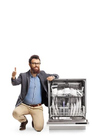 Bearded man kneeling next to a dishwasher and showing thumbs up isolated on white background 写真素材 - 124977074