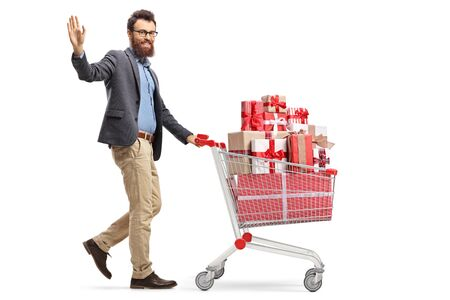 Full length shot of a bearded man waving and walking with a shopping cart full of presents isolated on white background