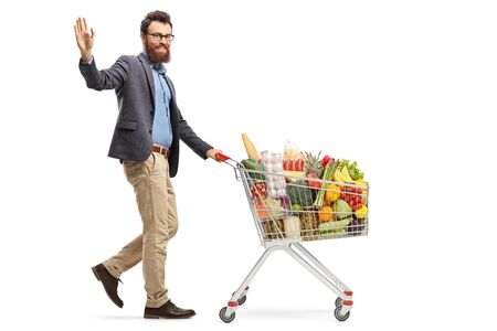Full length shot of a man walking with a shopping cart with food products and waving with hand isolated on white background 写真素材 - 124977077