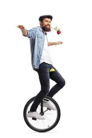 Full length shot of a bearded guy on a unicycle holding a red rose with his mouth isolated on white background