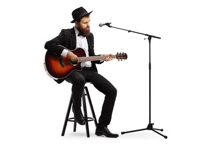Full length shot of a man playing an acoustic guitar with a microphone in front of him isolated on white background
