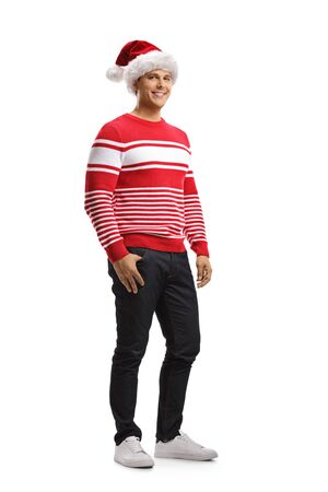 Full length portrait of a cheerful young man wearing a christmas santa hat and a red sweater isolated on white background Stockfoto - 124977082