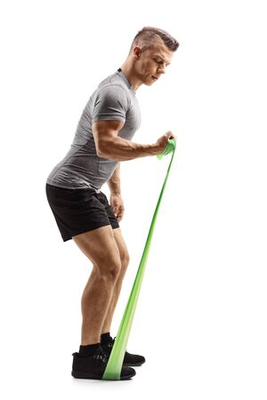Full length profile shot of a young muscular guy exercising with an elastic band isolated on white background Reklamní fotografie