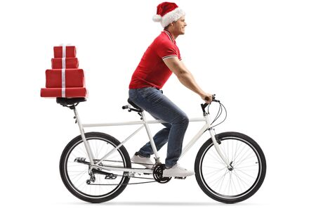 Full length shot of a young man with a christmas hat riding a tandem bicycle and carrying presents on the back seat isolated on white background
