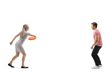 Full length shot of a young man and woman playing with a frisbee isolated on white background