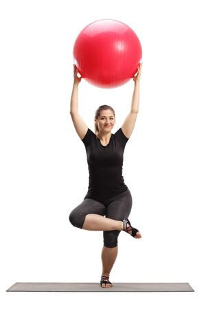 Full length portrait of a young woman lifting a fitness ball and exercising on a mat isolated on white background Reklamní fotografie