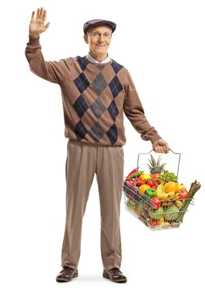 Full length portrait of a senior man carrying a full shopping basket and waving at the camera isolated on white background