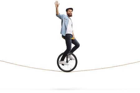 Full length shot of a bearded young man riding a unicycle on a rope and waving isolated on white background 写真素材 - 124977106