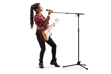 Full length shot of a female rock musician with a guitar singing on a microphone isolated on white background Stock Photo
