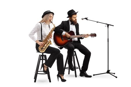 Full length shot of a young woman playing sax and a man playing an acoustic guitar isolated on white background Stock Photo