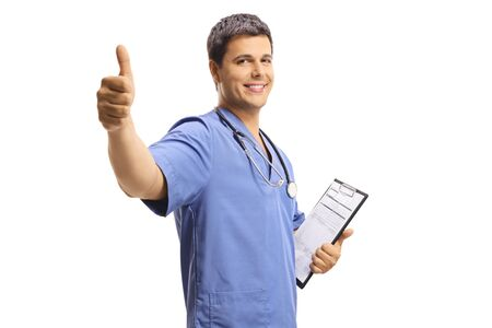 Young male doctor in a blue uniform holding a clipboard and showing thumbs up isolated on white background
