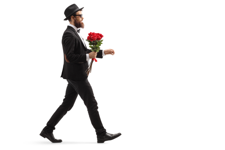 Full length profile shot of a bearded man in a suit walking with a bunch of red roses isolated on white background