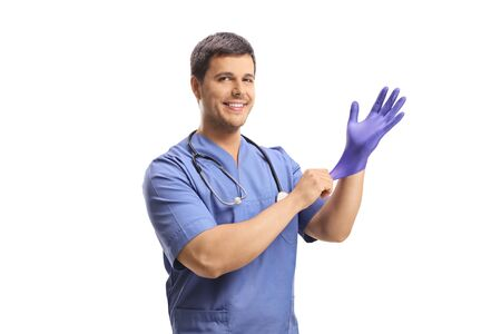 Smiling young male doctor putting a glove isolated on white background
