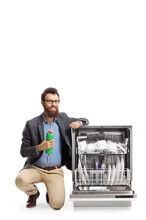 Man kneeling next to a dishwasher and holding a bottle of washing cleaning supply isolated on white background