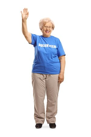 Full length portrait of an elderly lady volunteer waving at the camera isolated on white background 写真素材 - 124977115
