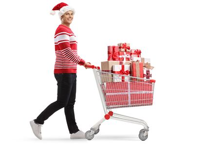 Full length profile shot of a young man with a shopping cart with presents wearing a santa hat isolated on white background
