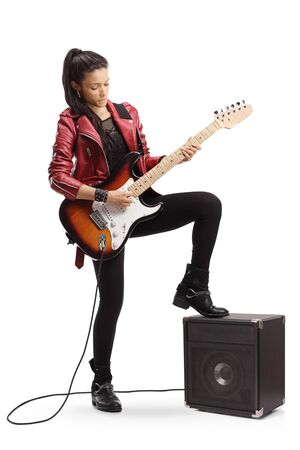 Full length portrait of a young female playing a bass guitar and standing next to an amplifier isolated on white background
