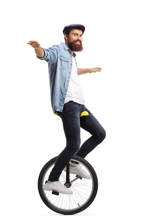 Full length shot of a bearded guy on a unicycle balancing with his hands isolated on white background