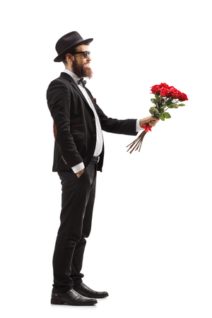 Full length profile shot of a man in a suit giving a bouquet of red roses isolated on white background