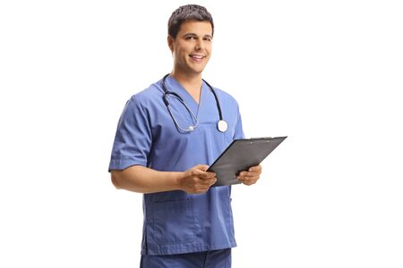 Portrait of a young male doctor in a blue uniform holding a clipboard and looking at the camera isolated on white background Reklamní fotografie