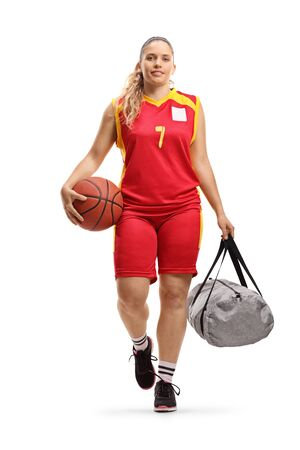 Full length portrait of a female basketball player in a jersey walking and carrying a ball and a sports bag isolated on white background Reklamní fotografie