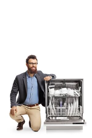 Bearded man kneeling next to a dishwasher and smiling at the camera isolated on white background Reklamní fotografie