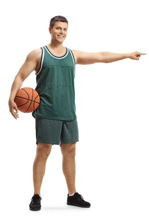 Full length portrait of a young male basketballer in a jersey holding a ball and pointing to one side isolated on white background