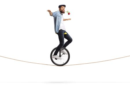 Full length shot of a bearded young man riding a unicycle on a rope and holding a red rose with his mouth isolated on white background