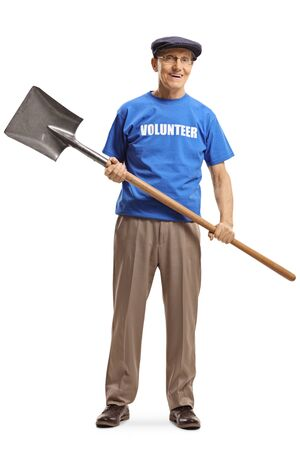 Full length portrait of a senior volunteer in a blue t-shirt holding a shovel and looking at the camera isolated on white background Reklamní fotografie
