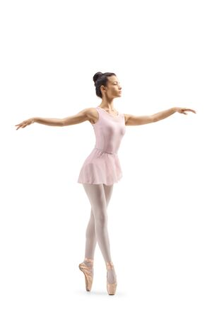 Full length shot of a young female ballet dancer dancing on tiptoes isolated on white background