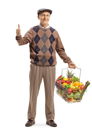 Full length portrait of a cheerful senior man with a full shopping basket showing thumbs up isolated on white background 写真素材 - 124977199
