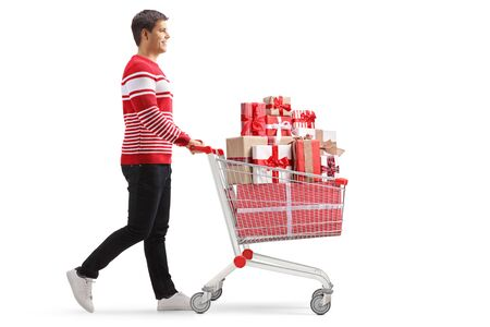 Full length profile shot of a young cheerful man pushing a shopping cart full of presents isolated on white background Reklamní fotografie