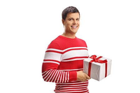 Young cheerful man holding a present isolated on white background