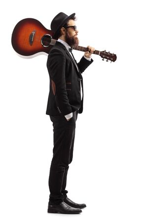 Full length profile shot of a man carrying an acoustic guitar on his shoulder isolated on white background
