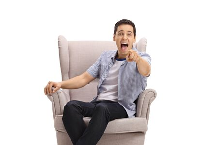 Young guy sitting in an armchair pointing at the camera and laughing out loud isolated on white background Reklamní fotografie